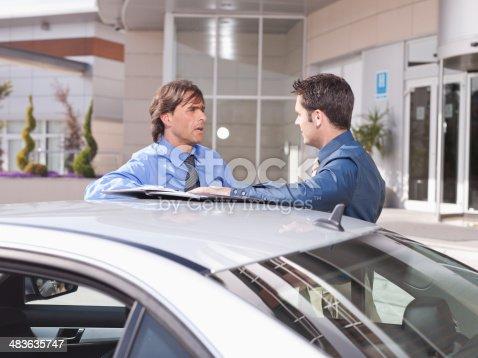 istock Businessmen talking near car 483635747
