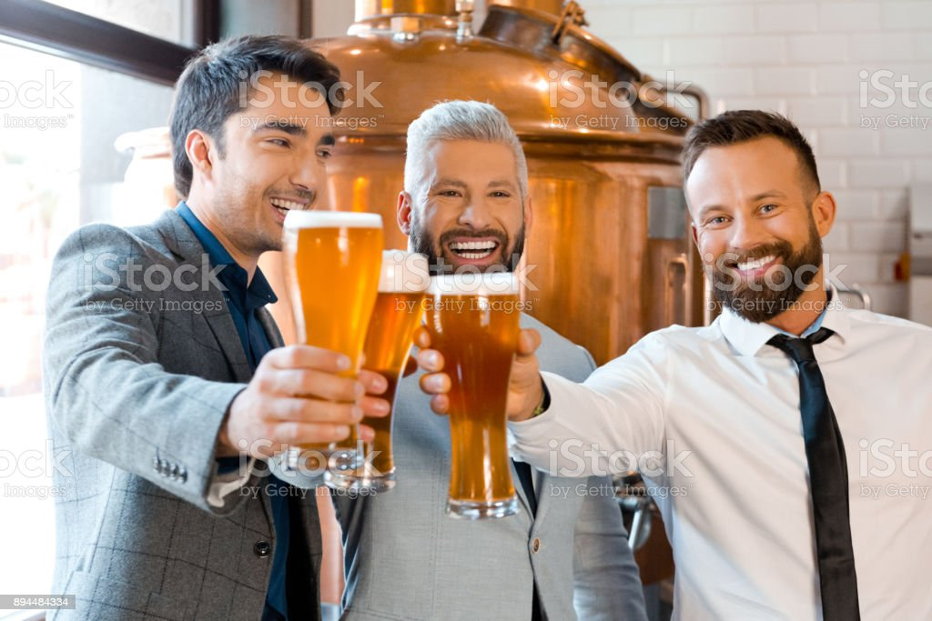 Businessmen toasting with beer in micro brewery Portrait of three businessmen toasting with beer in micro brewery. Businesspeople celebrating success with beers at brewery. Adult Stock Photo
