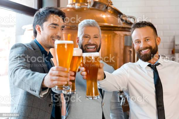 Businessmen Toasting With Beer In Micro Brewery Stock Photo - Download Image Now
