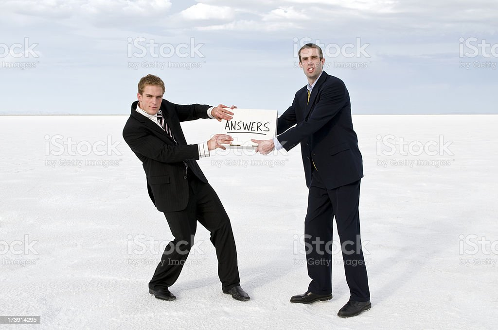 Businessmen tugging at answers stock photo