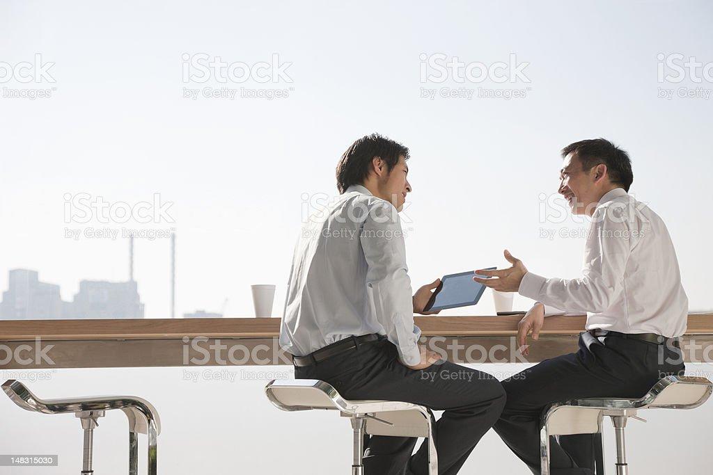 Businessmen using digital tablet in meeting royalty-free stock photo