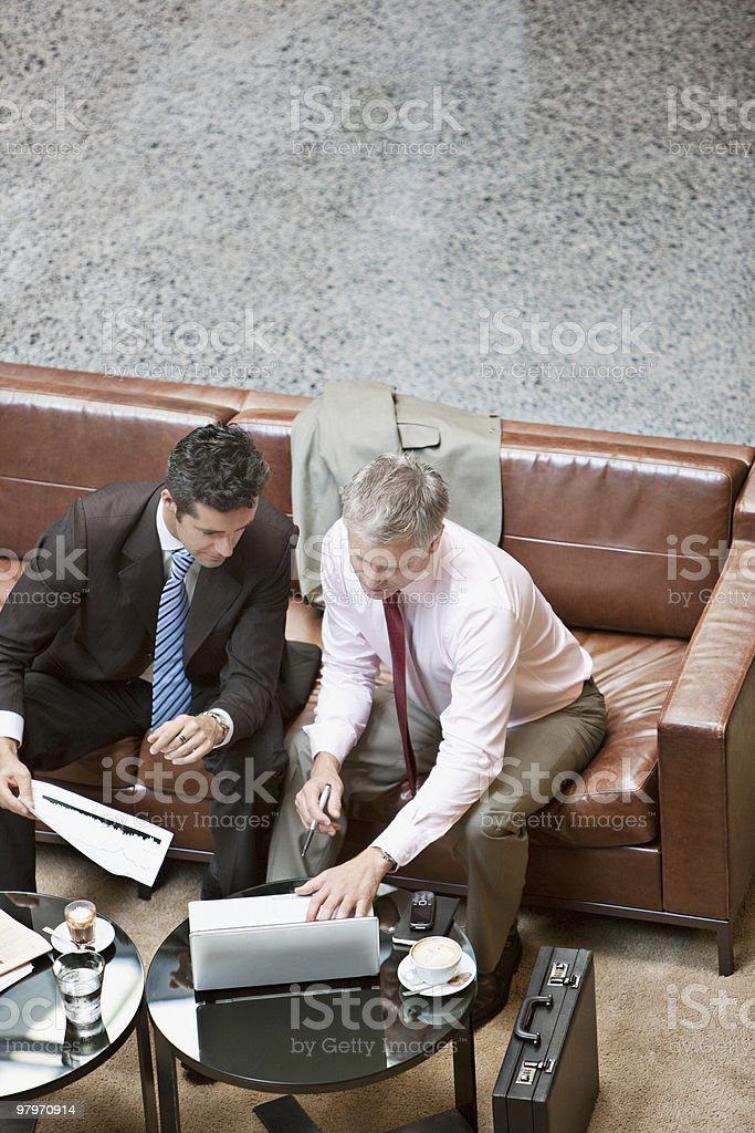 Businessmen using laptop in lobby royalty-free stock photo