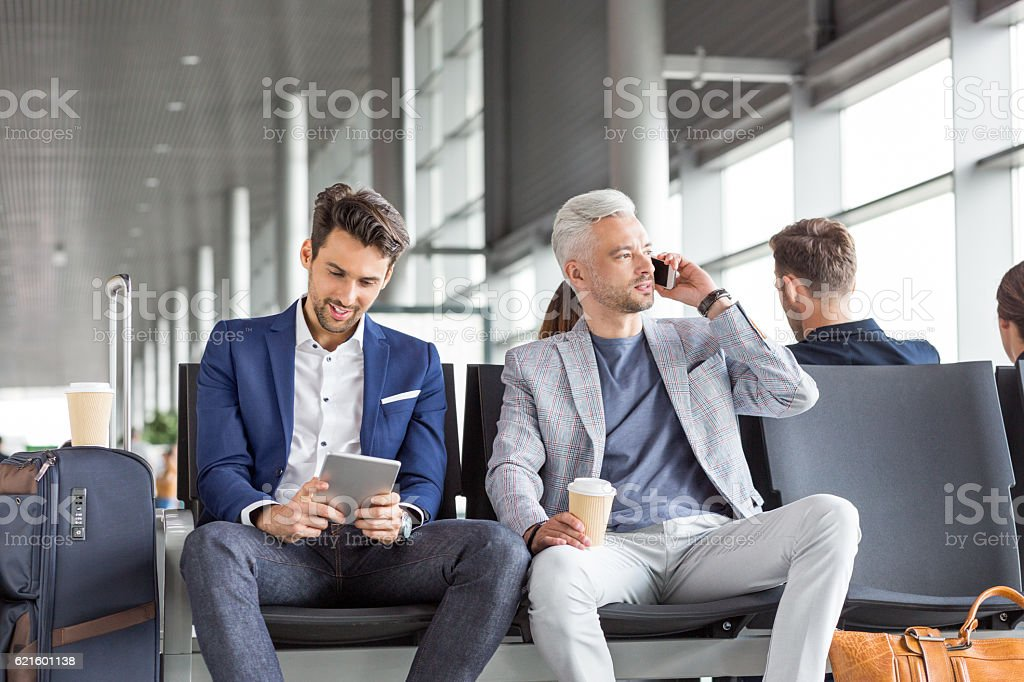 Businessmen waiting for flight at airport lounge stock photo