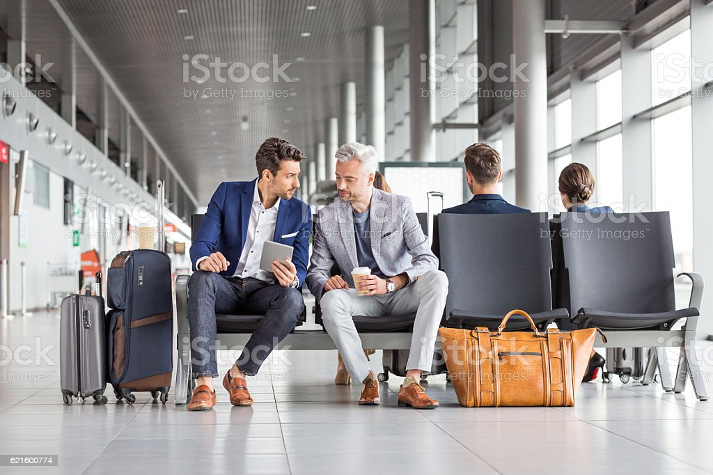 Businessmen waiting for their flight Two businessmen waiting for their flight at the airport lounge, using a digital tablet with people sitting at the back. Adult Stock Photo