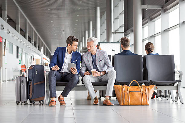 businessmen waiting for their flight - business travel stock photos and pictures