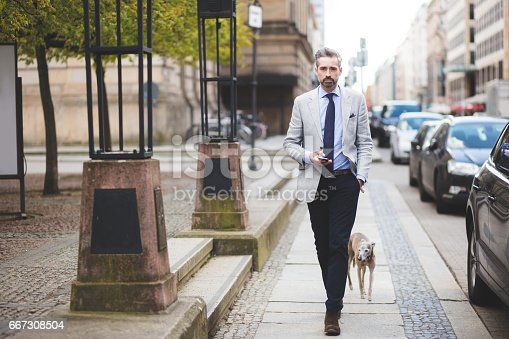 istock Businessmen walking with dog in city 667308504