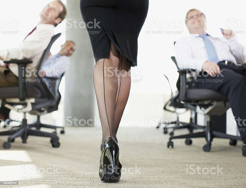 Businessmen watching sexy co-worker stock photo
