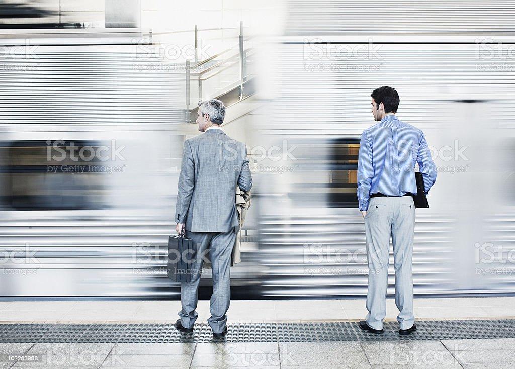 Businessmen watching speeding train stock photo