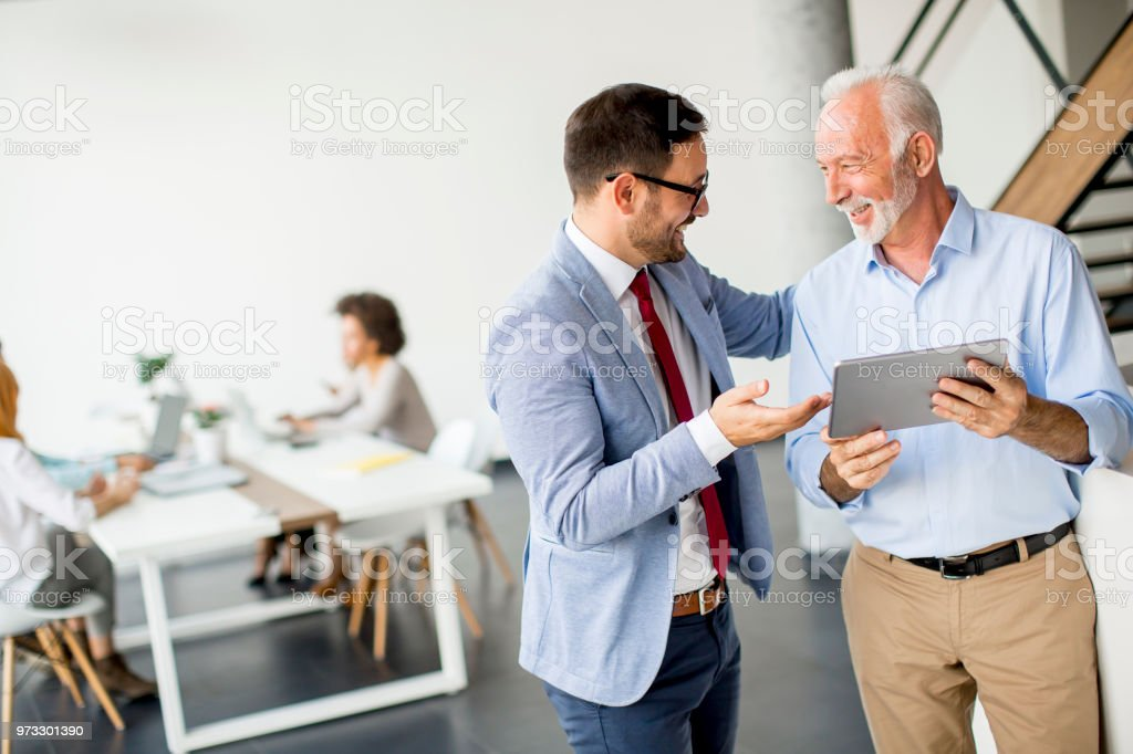 Businessmen with digital tablet in office - Royalty-free Active Seniors Stock Photo