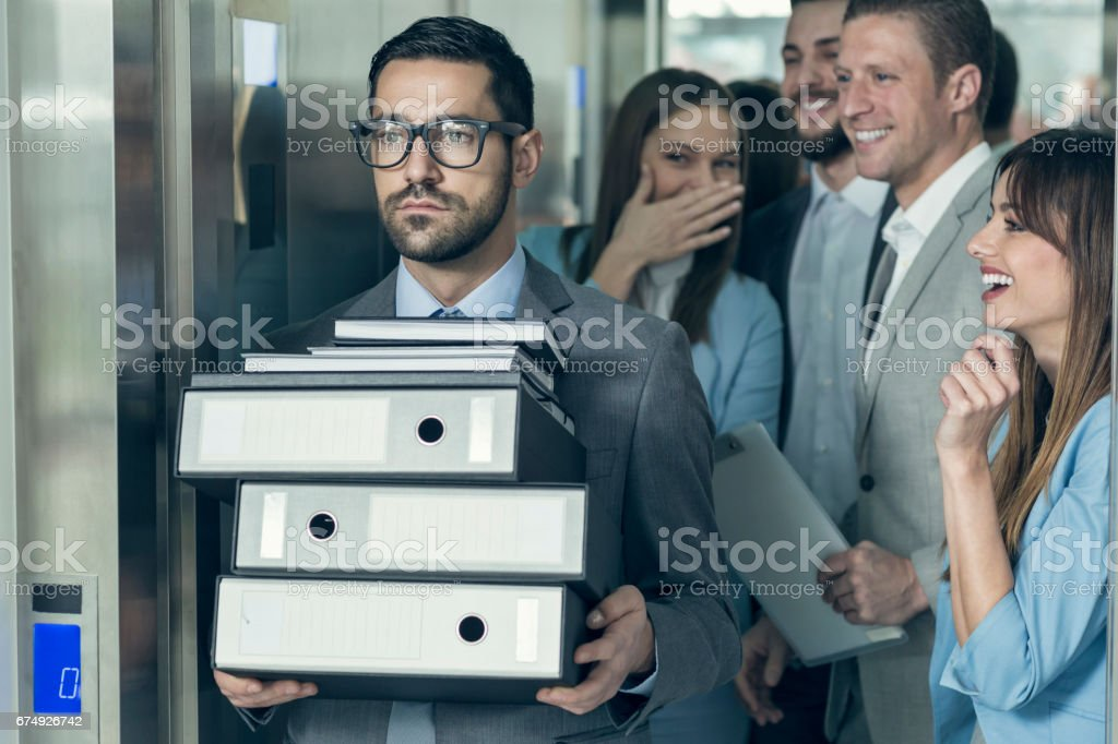 Businessmen with hands full of documents walking out of elevator while his collegues gossip behind his back royalty-free stock photo