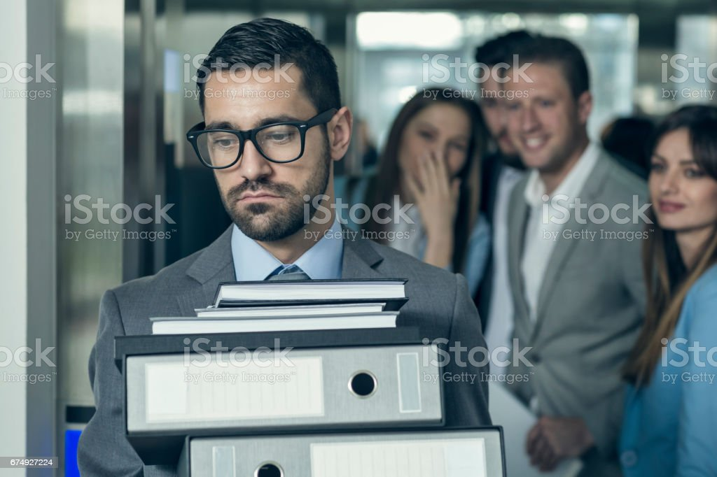 Businessmen with hands full of documents walking out of elevator while his collegues gossip behind his back - Photo