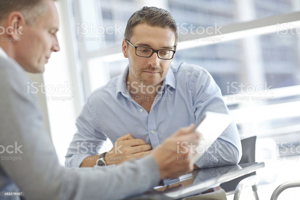 Businessmen with tablet during meeting stock photo