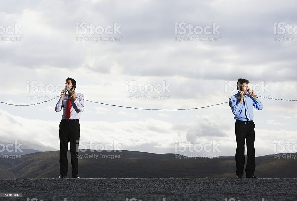 Businessmen with telephone receivers joined outdoors royalty-free stock photo