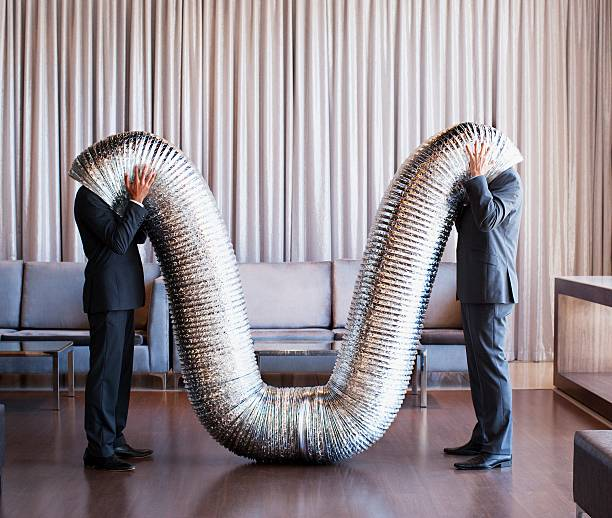 businessmen with their heads inside metal tubing - humor stock photos and pictures
