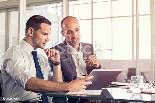 Businessman using a digital tablet to discuss information with senior leadership in a meeting. Business partners discussing plans. Mature boss and young business man working together in office.