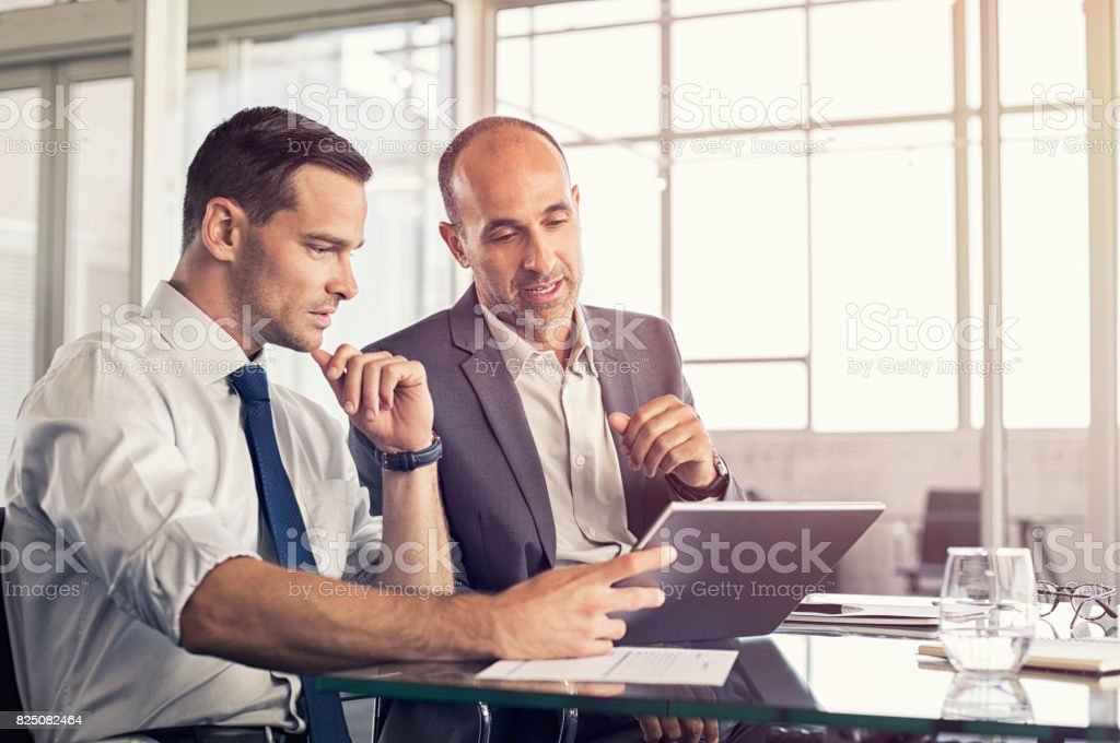 Businessmen working on digital tablet stock photo