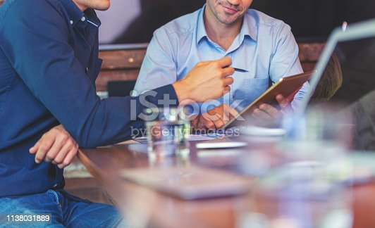 Businessmen working together on a digital tablet. They are both wearing smart casual clothing and having a conversation. Both are unrecognizable. There are other documents a laptop computer and mobile phones on the table