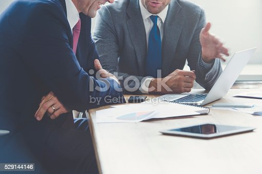istock Businessmen working together on a laptop. They are both wearing suits and having a conversation. One man is smiling but both are unrecognizable. There are other documents a laptop computer and mobile phones on the table 529144146