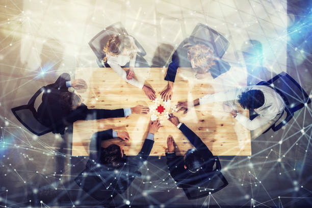 Businessmen working together to build a colored puzzle. Concept of teamwork, partnership, integration and startup. Double exposure with network effects - foto stock