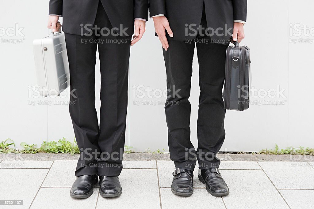 Businessmens legs and holding briefcases royalty-free stock photo