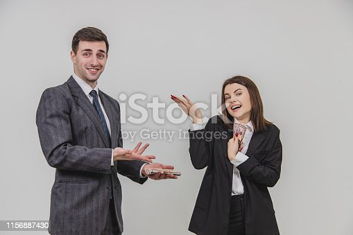 istock Businesspartners standing, dividing money. Man is confused. Woman is looking carelessly, holding hand with banknotes close to the chest. 1156887430