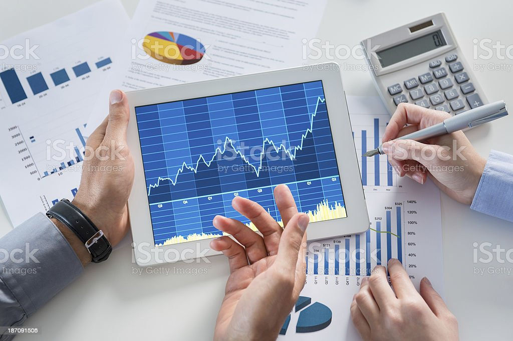 Businesspeople Analyzing Graph With Digital Tablet stock photo