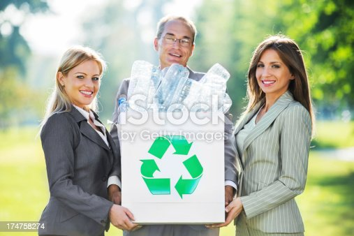 Cheerful businesspeople holding a box full of plastic bottles.  Environmental conservation.