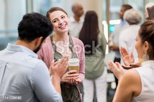 Young businesswoman has a humble expression on her face as her colleagues applaud after a presentation.