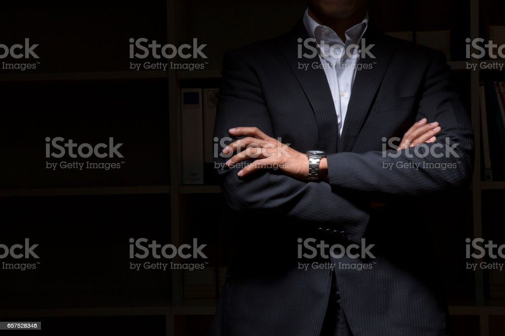 Businesspeople arm in arm in the darkness stock photo