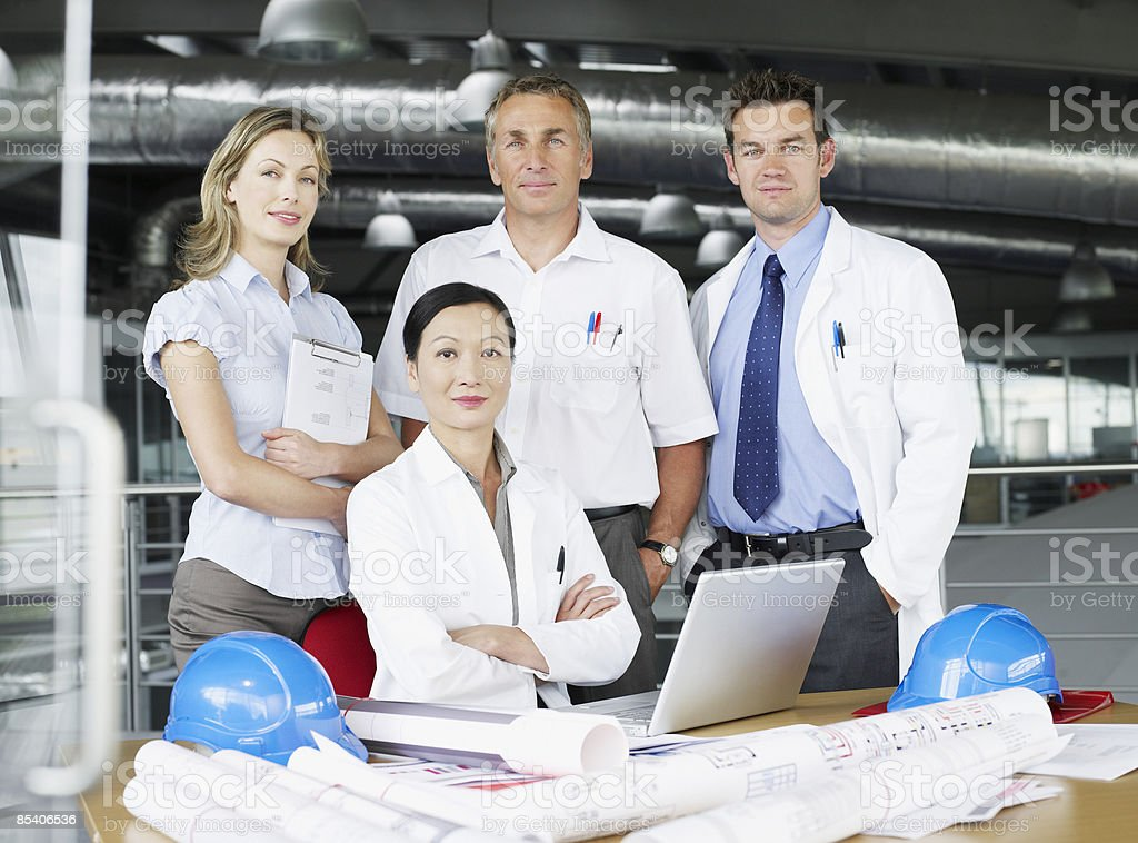 Businesspeople at desk with blueprints royalty-free stock photo