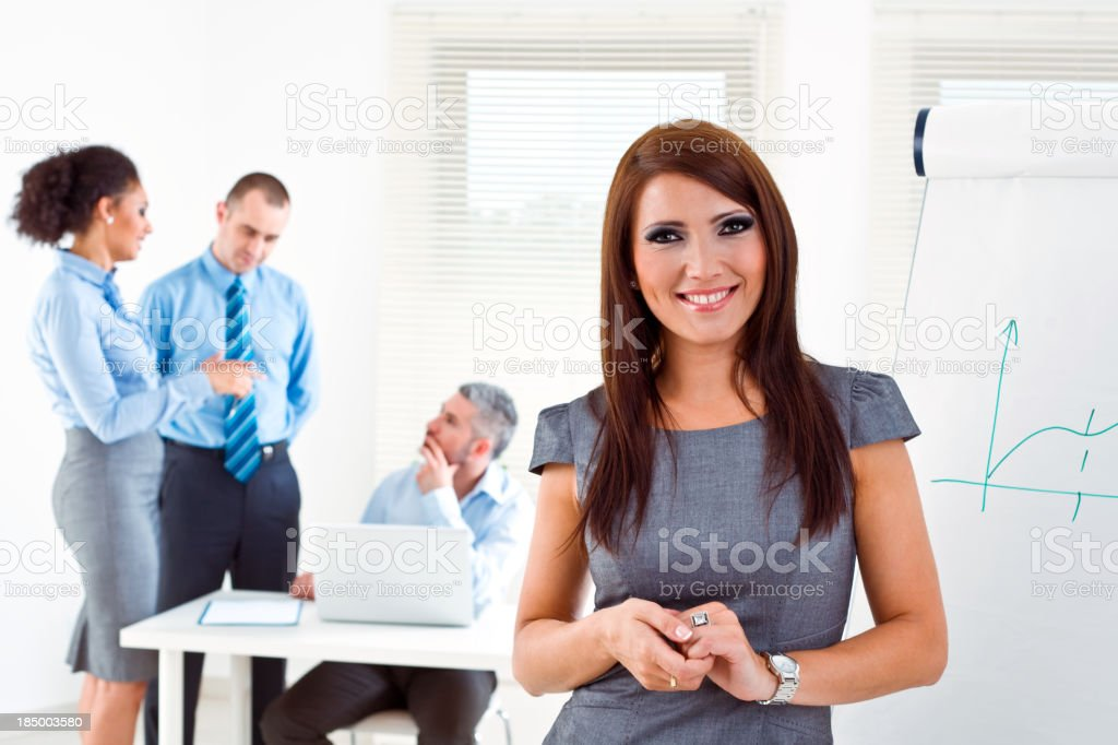 Businesspeople at work Focus on the young businesswoman standing next to the flip chart and smiling at camera with her colleagues working in the background. Adult Stock Photo