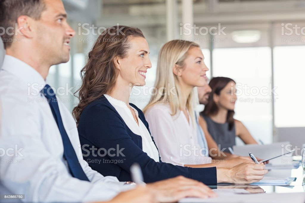 Businesspeople attend at seminar stock photo