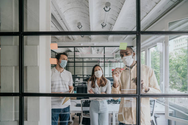 Businesspeople brainstorming during the Covid-19 pandemic stock photo