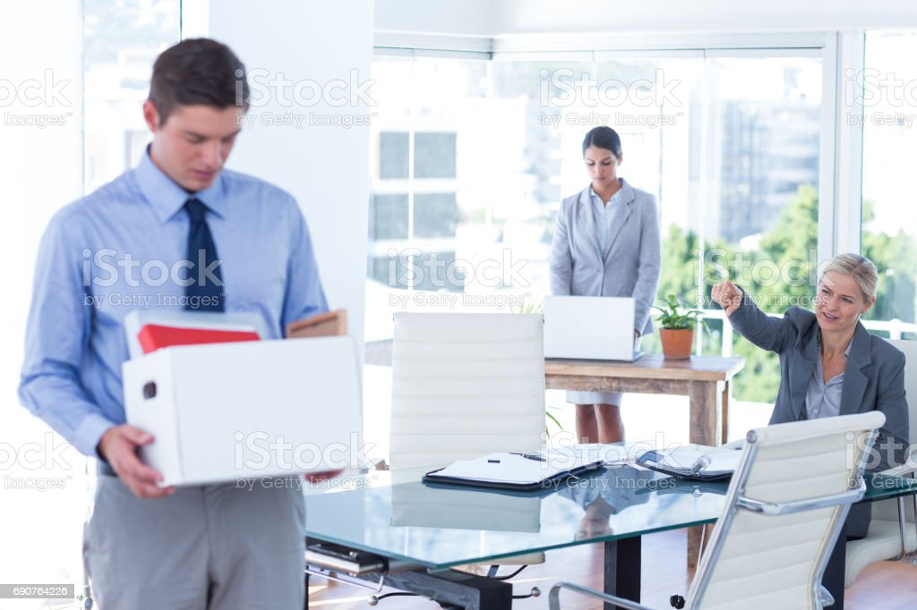 Businesspeople carrying their belongings in box stock photo