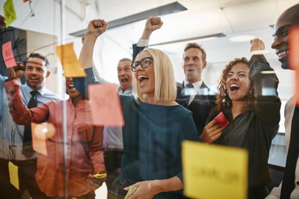 geschäftsleute, die jubeln beim brainstorming mit haftnotizen in einem büro - jubeln stock-fotos und bilder