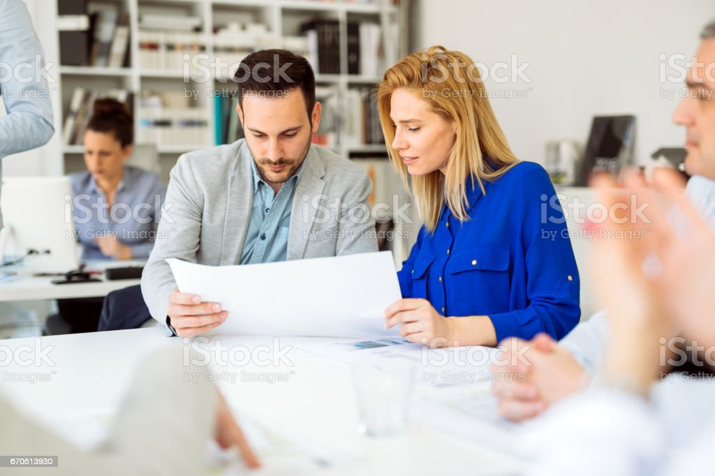 Businesspeople collaborating and talking through new ideas in office stock photo