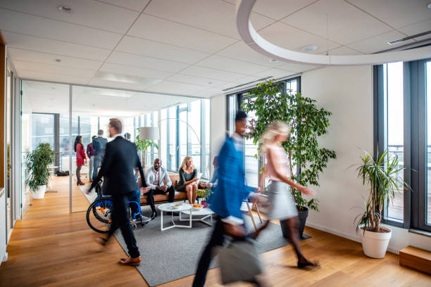 Businesspeople Coming and Going Through Office Lobby stock photo