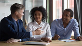 Businesspeople discussing contract conditions before signing at meeting, manager or realtor consulting African American clients in office, successful negotiations concept, hiring process