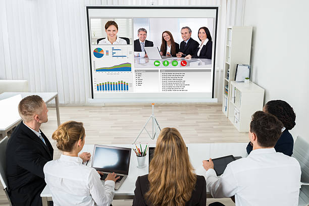 Businesspeople Discussing Graphs Through Videochat stock photo
