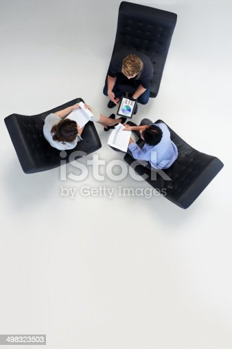 High angle view of businesspeople discussing over documents in meeting at office