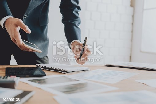 975599364istockphoto Businesspeople discussing the charts and graphs,businessmen discussing on stockmarket document in office,Business concept. 975599106