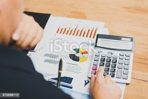 975599364istockphoto Businesspeople discussing the charts and graphs,businessmen discussing on stockmarket document in office,Business concept. 975599112