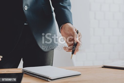 975599364istockphoto Businesspeople discussing the charts and graphs,businessmen discussing on stockmarket document in office,Business concept. 975599176