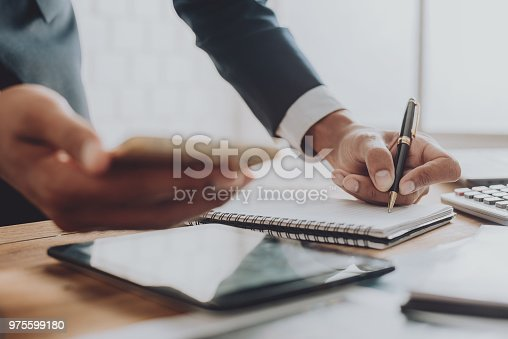 975599364istockphoto Businesspeople discussing the charts and graphs,businessmen discussing on stockmarket document in office,Business concept. 975599180