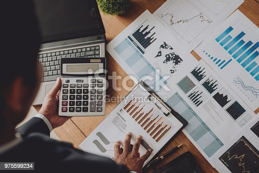 975599364istockphoto Businesspeople discussing the charts and graphs,businessmen discussing on stockmarket document in office,Business concept. 975599234