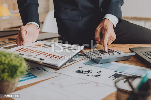 975599364istockphoto Businesspeople discussing the charts and graphs,businessmen discussing on stockmarket document in office,Business concept. 975599266