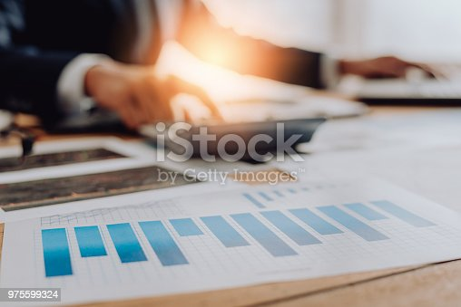 975599364istockphoto Businesspeople discussing the charts and graphs,businessmen discussing on stockmarket document in office,Business concept. 975599324