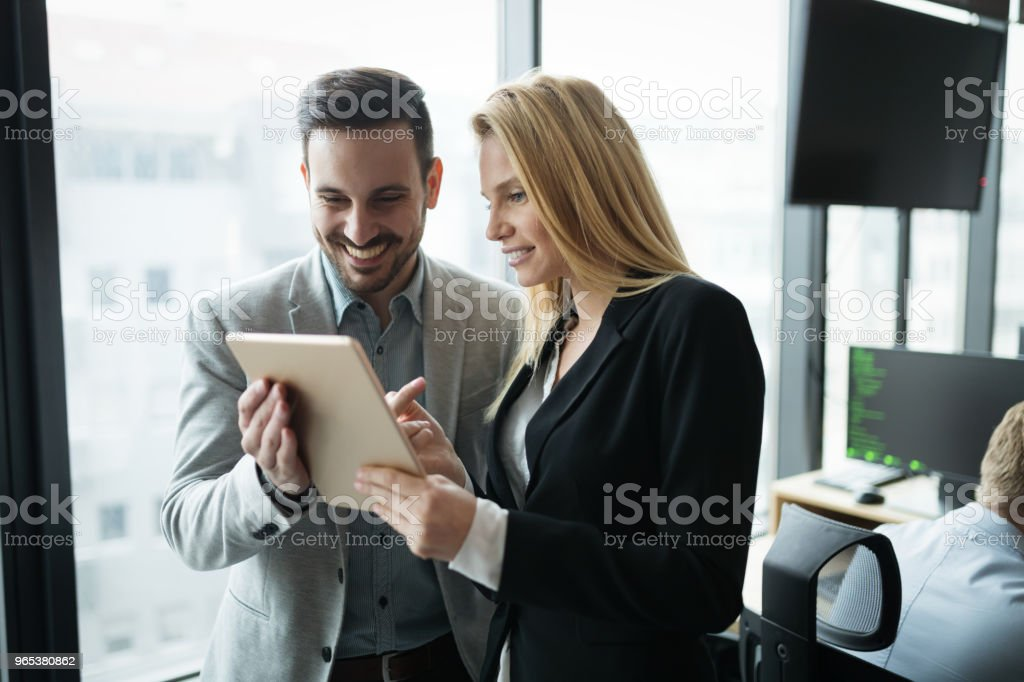 Businesspeople discussing while using digital tablet in office - Zbiór zdjęć royalty-free (Biuro)