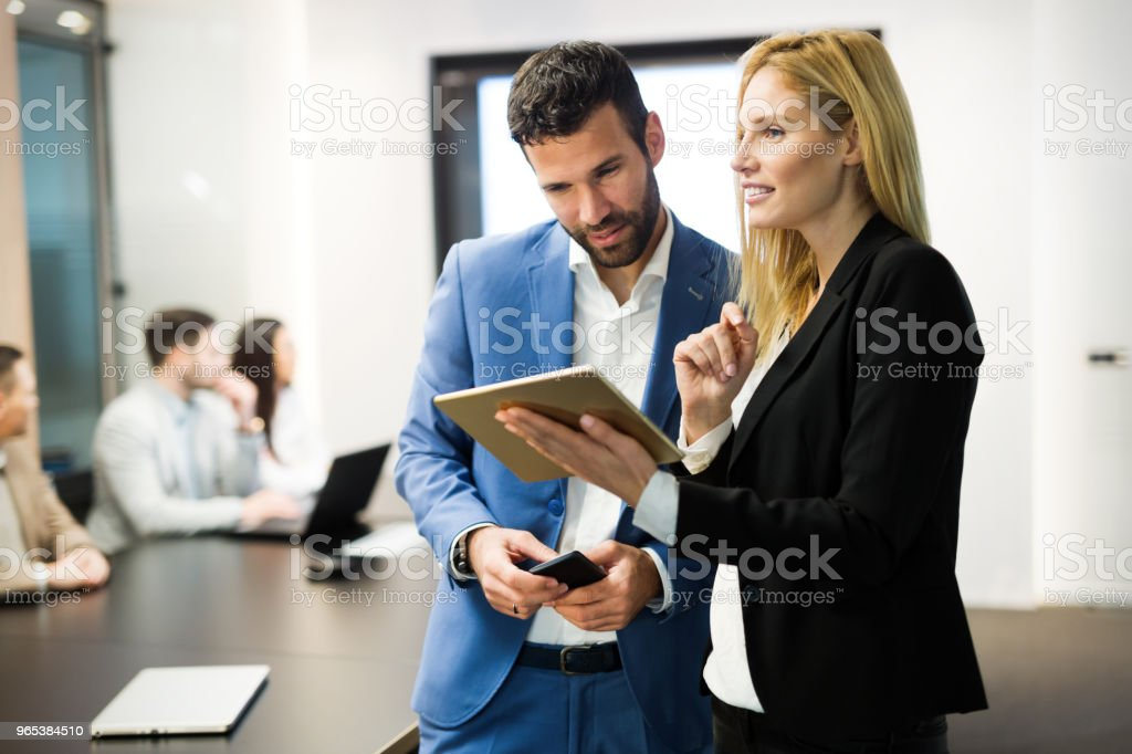 Businesspeople discussing while using digital tablet in office zbiór zdjęć royalty-free