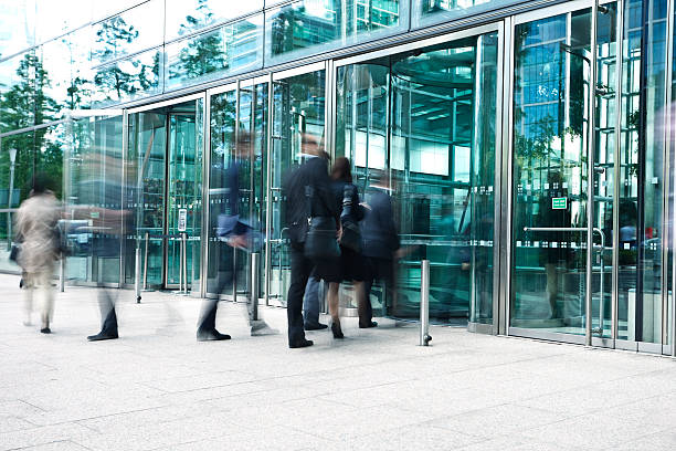 businesspeople entering through glass doors of office building, blurred motion - entrance stock photos and pictures